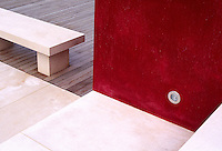 Red Venetian plaster wall terraces a contemporary garden, the simple geometeric design shows off the limestone steps and bench with Cedar wood decking and recess light.