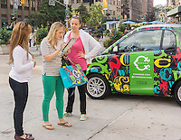 A worker, left,  for the store C. Wonder engages with consumers and collect data using an iPad at an event in Madison Square in New York on Saturday, September 20, 2014. C. Wonder was promoting their new store in the Flatiron neighborhood using decorated Smart Cars, one filled with gumballs for visitors to guess the amount.  (© Richard B. Levine)