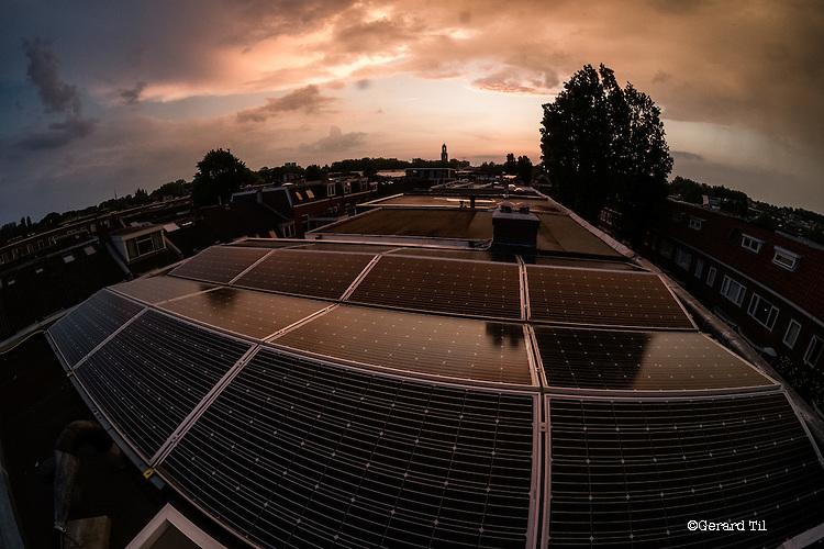 Nederland,Utrecht,   04-05-2016 Zonnepanelen  op het dak van een rijtjeshuis uit 1930 in de Utrechtse wijk Oudwijk. Op de achtergrond de Domtoren .FOTO: Gerard Til / Hollandse Hoogte