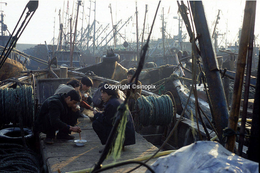 Migrant workers from Henan province have breakfast on their fishing boats at the harbour at Chuwang fishing village 250 km away from Beijing. The Chinese fishing industry is in decline with the government cut of 10% of boats, which amounts to 10,000 boats and 30,000 fishermen. Most boats in Chuwang have not been put to sea for two weeks. Penglai, China.<br /> 26-JAN-02