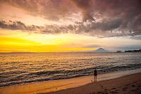 A lone person on the beach looking toward Bali and Gunung Agung, Bali's sacred mountain.
