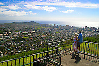 A young couple enjoys this panaramic view of Diamond  Head and surrounding skyline area from atop Puu Ualakaa Park and Wayside.