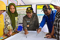 Bunda Frederica Bawoyle (Kepala Desa) with village members and representatives from the Womens' Association (PKK) during a meeting discussing land use in the area, Tabula Selatan, Gorontalo, Sulawesi, Indonesia.