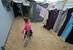 A Syrian girl rides her bike as her mother hangs laundry outside their family's shelter in the Zaatari refugee camp near Mafraq, Jordan. Established in 2012 as Syrian refugees poured across the border, the Zaatari camp held more than 80,000 refugees by 2015, and was rapidly evolving into a permanent settlement. ACT Alliance member agencies provide a variety of services to refugees living in the camp.
