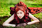 Redhead in Victorian dress laying on grass