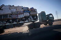 November 22, 2014 - Murzuq region, Libya: A truck heavily loaded with goods heading to the border stops at a black market area in the middle of the desert in Southwest Libya. Libya's borders remain largely ungoverned, and securing the periphery is among the country's greatest challenges. Weak border control allows markets in arms, people, and narcotics to thrive alongside everyday trafficking in fuel and goods, with profound consequences for the region as a whole. (Photo/Narciso Contreras)