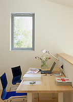 A shared study with two blue office chairs at the contemporary table is kept simple and uncluttered