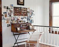 An antique desk and armchair have been arranged on a corner of the landing to serve as a compact office space