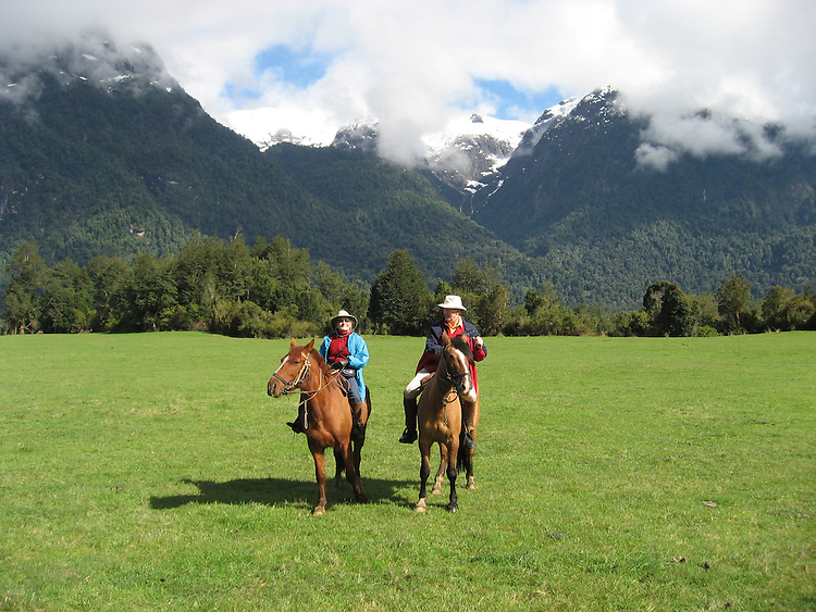 Chile, Lake Country: People riding horses at Peulla in a meadow in the Andes..Photo #: ch613-264..Photo copyright Lee Foster www.fostertravel.com, lee@fostertravel.com, 510-549-2202.