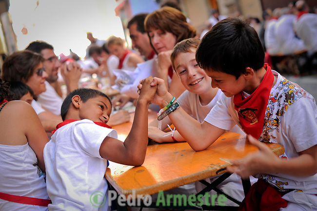 Children play during the San Fermin Festival, on July 13, 2012, in Pamplona, northern Spain. The festival is a symbol of Spanish culture that attracts thousands of tourists to watch the bull runs despite heavy condemnation from animal rights groups . (c) Pedro ARMESTRE