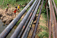 Three young children play beneath some old pipelines, near the Auca Road, used by Petro Amazones to transport oil out of the jungle.