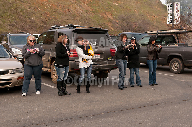 Spectators watch as shotgun-toting locals gather at Mel's Drive-in restaurant to fire off rounds during Jackson, California's Serbian community celebrates Christmas on the Julian Calendar date of January 7.