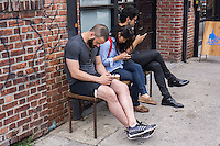 Hipsters preoccupied with their smartphones outside a coffee shop in the trendy hipster Williamsburg neighborhood of Brooklyn in New York on Saturday, June 8, 2013. © Richard B. Levine)