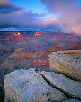 Grand Canyon National Park, AZ: Evening sunlight breaks through gathering clouds to light the peak of Zoroaster Temple - from the South Rim near Yavapai Point