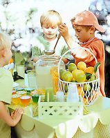 A boy serving homemade lemonade to his friend from his lemonade stand