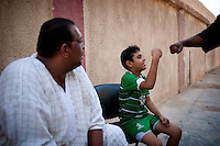 Ahmed, 12, greets his coach before the ritual of the weighing which     is practised every other day.