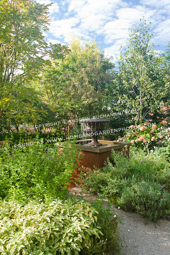 Mixed planting beds surround the curved stone path that leads to the fountain in this peaceful Seattle yard.