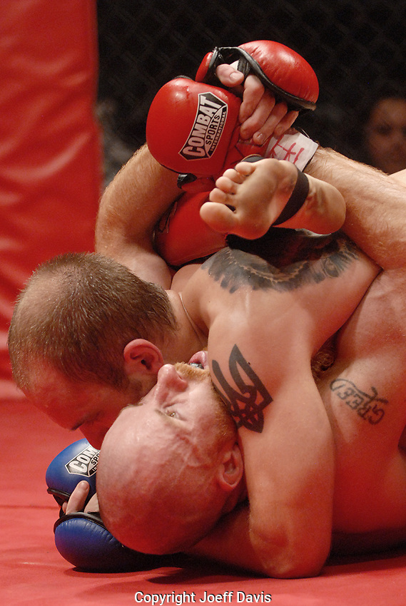 """A fighter's leg is awkwardly bent bent during a cage wrestling fight at Sin City Fight Club's """"Showdown at Center Stage,"""" in Atlanta."""