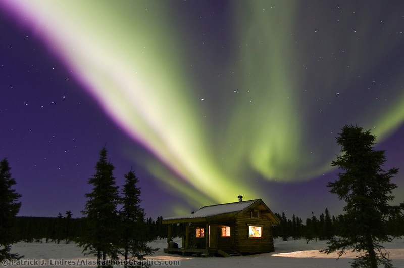 Aurora borealis swirls across the sky over Moose Creek cabin, in the White Mountains National Recreation Area, interior, Alaska.