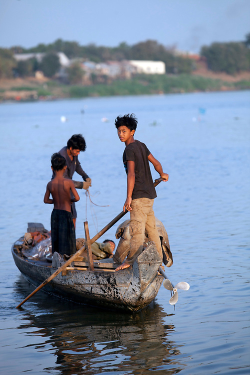 Young fisherman work the Mekong River early in the morning outside of Phnom Penh, Cambodia. <br /> <br /> Photos &copy; Dennis Drenner 2013.