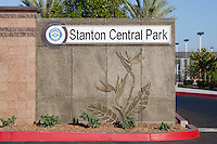 The entrance sign to Stanton Central Park, with the tennis courts and multiple plants visible in the background.