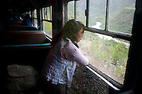 A passenger looks out the window as the train rides along the Mantaro River.