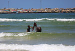 A Palestinian boy washes his donkey as he swims at the beach of Gaza city on April 30, 2015. Photo by Ashraf Amra