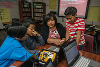 NWA Democrat-Gazette/ANTHONY REYES @NWATONYR<br /> Volunteer Elvira Ramirez-Careaga helps, (from left) Beejay Michael, 12, Manini Laikidrik, 12, and Ishmael Bunglick, 12, with their homework Monday, Feb. 27, 2017 at an after school tutoring session at Hellstern Middle School in Springdale. On this day, they were getting started on their homework list for the week.