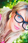 Close up of young woman with blonde hair in pigtails wearing large funny glasses