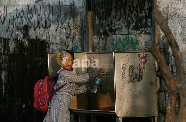 A Palestinian girl fills a water bottle from a public tap in Rafah refugee camp in southern Gaza Strip, Oct. 30, 2013. The United Nations Relief and Works Agency for Palestine Refugees (UNRWA) has removed food aid for 9,558 families in Gaza since the beginning of the year, while adding only 5,430 new families to the programme. Photo by Eyad Al Baba