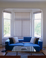 A large blue sofa in the bay window has moveable elements to accommodate different seating positions
