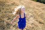 A happy young woman, wearing a blue summer dress, spins around in the sunshine in a park.