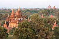 Myanmar, Burma, Bagan.  Tourists Watch the Sunrise from a Temple Platform.