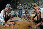 "Manggarai workers -- and their dog -- sift sediments from a Liang Bua excavation pit in search of tiny remains at the discovery site of Homo floresiensis. the Flores ""hobbit"" Reasercher Thomas Sutikna looks on."