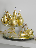A group of gilded pears in a glass sweet tray on the mantelpiece