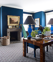 The walls of Trevor's study are covered in a royal blue cotton matched with a geometric carpet and display more of his collection of artwork