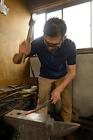 """An artisan forging a handle for a """"tansu"""" chest of drawers, Iwayado, Oshu City, Iwate Prefecture, Japan, July 19, 2013. Iwayado Tansu chests of drawers have been made in the city of Oshu since the 1780s. They are noted for their fine lacquer finish and finely-wrought metalwork fittings."""