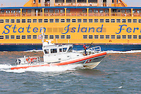 US Coast Guard Response Boat-Medium (RB-M) 45612 passes by the Staten Island Ferry on a mission in New York Harbor