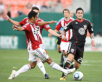 Santino Quaranta #25 of D.C. United moves the ball away from Michael Umana #4 and Ben Zemanski #21 of Chivas USA during an MLS match at RFK Stadium, on May 29 2010 in Washington DC. United won 3-2.