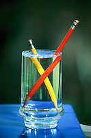 REFRACTION OF LIGHT - IN GLASS OF WATER<br /> Refraction: Pencils<br /> Light rays passing from one medium to another are refracted at the boundary between the two media.  The image of two pencils is refracted by both the air-glass media and the glass-water media.