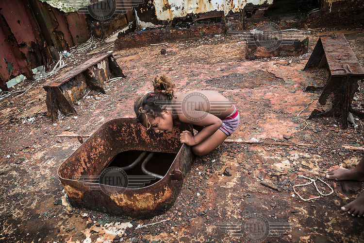 Tokorubi, six, looks into the hold of a wrecked ship which was lifted and smashed onto the town's sea wall during a king tide in February 2015.