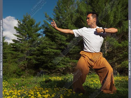 Portrait of a man practicing sunrise Qi Gong outdoors in green summer nature scenery. Qigong, chi kung, chi gung. Instructor Shi Chang Dao,  Shaolin Temple STQI Toronto.