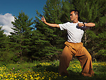 Portrait of a man practicing sunrise Qi Gong outdoors in green summer nature scenery. Qigong, chi kung, chi gung. Instructor Shi Chang Dao,  Shaolin Temple STQI Toronto.