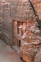Treasury of the Pharaohs or Khazneh Firaoun, 100 BC - 200 AD, with plaza in front, Petra, Ma'an, Jordan. Originally built as a royal tomb, the treasury is so called after a belief that pirates hid their treasure in an urn held here. Carved into the rock face opposite the end of the Siq, the 40m high treasury has a Hellenistic facade with three bare inner rooms. Petra was the capital and royal city of the Nabateans, Arabic desert nomads. Man walking below shows the scale of the edifice. Picture by Manuel Cohen