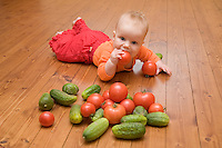 Five month old caucasian baby on wooden floor and eating tomato. Floorboard. Vegetables.