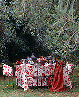A table laid for an autumnal supper in the garden under the olive trees