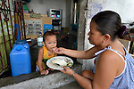 """In the capital of the Philippines, a mother feeds her child in the doorway of a mausoleum that doubles as their home in the Manila North Cemetery. Hundreds of poor families live here, dwelling in and between the tombs and mausoleums of the city's wealthy. They are often discriminated against, and many of their children don't go to school because they're too hungry to study and they're often called """"vampires"""" by their classmates. With support from United Methodist Women, KKFI provides classroom education and meals to kids from the cemetery at a nearby United Methodist Church."""