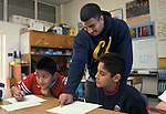 Berkeley CA Latino unvierstiy student volunteer helping latino students with writing in 4th grade class