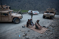 Men pray at the site of a roadside bomb next to a US Army Humvee near Naray village in Kunar. The HHT Unit of the 3rd Brigade Combat Team, 1st Infantry Division responded to an IED (improvised explosive device) attack on a coalition supply convoy. The bomb destroyed a supply truck carrying Humvee spare parts.