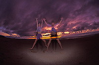 A couple jumps with arms outstretched on the sand against a background of pink and purple clouds.